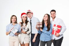 Celebration of New Year or Christmas. Group of cheerful young people with gifts on a white background Stock Photos