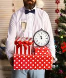 Celebration and New Year decor concept. Guy near Christmas tree. On wooden wall background. Man with beard and bow tie holds present boxes, champagne glass and royalty free stock photo