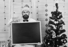 Celebration and New Year mood concept. Guy near Christmas tree. On wooden wall background. Man with beard holds blank blackboard and points at it, copy space stock photo