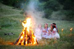 The celebration of the pagan Slavic holiday of Ivan Kupala Day or Midsummer. Young girls in white shirts and wreaths of flowers on the background of a fire. The Stock Photography