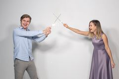 Celebration, party and holiday concept - Portrait of young couple fooling around with sparklers royalty free stock photo