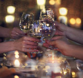 Celebration. People holding the glasses of white wine making a t. Oast. Cozy evening in a restaurant Stock Photos