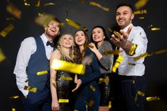 Happy friends at party under confetti over black Stock Photos