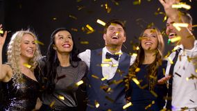 Happy friends at party under confetti over black. Celebration, people and holidays concept - happy friends at party under golden confetti over black background stock video footage