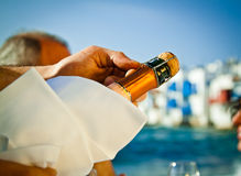 Celebration on the sea. Popping a bottle of champagne open by the sea Royalty Free Stock Image