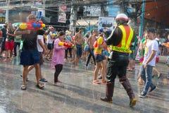 Celebration of Songkran Festival, the Thai New Year on Phuket. Phuket, Thailand - April 13, 2014: Tourist and police officer celebrate Songkran Festival, the Royalty Free Stock Photo