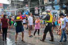 Celebration of Songkran Festival, the Thai New Year on Phuket. Phuket, Thailand - April 13, 2014: Tourist and police officer celebrate Songkran Festival, the stock photo