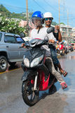 Celebration of Songkran Festival, the Thai New Year on Phuket. Phuket, Thailand - April 13, 2014: Two Thai on moped drive wet because of celebration Songkran stock image