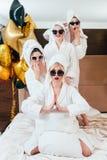 Celebration spa party fun women posing bathrobes. Celebration at spa. Party fun and relaxation. Smiling women posing on bed. Sunglasses, bathrobes and towel stock photo