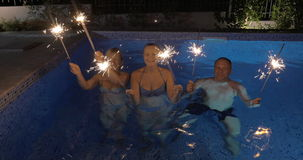 Celebration with sparklers in the swimming pool. Happy people of two women and a man dancing in outdoor pool with Bengal fires at night. Holiday celebration stock video