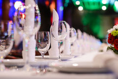 Celebration table setting for party in restaurant. Empty wine glasses, plates and napkins on a table in a restaurant royalty free stock photography