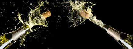 Celebration theme with explosion of splashing champagne sparkling wine bottles on black background.  stock photo