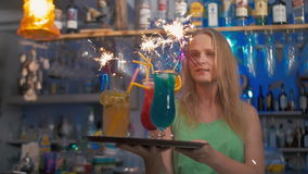 Celebration time with cocktails and sparklers. Slow motion of a young happy woman carrying the tray with cocktails in the bar. Sparklers burning in the glasses stock video footage