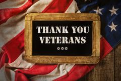 Celebration of Veterans Day. Close-up of USA flag in grunge design with wooden blackboard stock photo