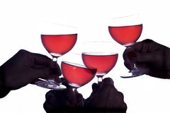 Celebration and wine. Silhoutted hands with glasses raised in a toast/celebration royalty free stock photography