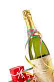 Celebrations kit. Champagne bottle with gifts, ribbons and confetti for celebrations. Shallow depth of field royalty free stock photos
