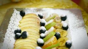 Celebratory beautiful dessert dish fruit assortment, kiwi banana mandarin powdered sugar concept food design stock video