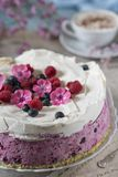Celebratory cake with berries and a cup of aromatic coffee. Vintage napkin, spoon and pink flowers royalty free stock image