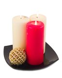 Celebratory candles. Celebratory burning light and red candles in black plate on white background Royalty Free Stock Images