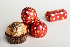 Celebratory composition from sweets. Chocolate golden sphere lay near a group of sweets in a red metallic paper with golden stars on white background Royalty Free Stock Photos