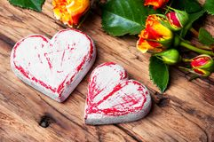 Symbolic wooden heart and flowers Stock Photos