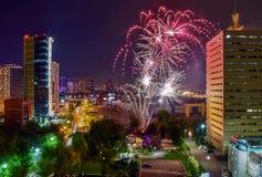 Celebratory fyrverkerier över nattstad med moderna byggnader av exponeringsglas och betong Fotografering för Bildbyråer