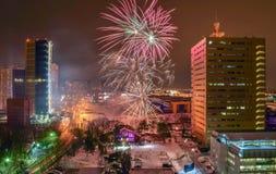 Celebratory fyrverkerier över nattstad med moderna byggnader av exponeringsglas och betong Arkivbild