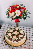 Celebratory homemade chokolate cake decorated with cream roses and red-white rose bouquet on table covered by macrame Royalty Free Stock Photo