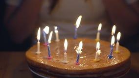 Celebratory kaka med tända stearinljus på bakgrunden av en kvinna lager videofilmer