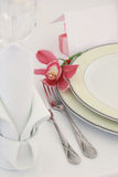 Celebratory plate. Celebratory yellow plate with plugs and an orchid a plate Royalty Free Stock Photos