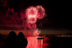 Celebratory red firework and people stock photography