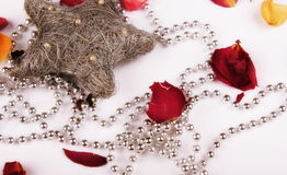 Celebratory still-life. Beads, asterisk and petals of roses on a mirror background Royalty Free Stock Image