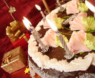 Celebratory table (birthday cake and candles, gift boxes) on red Royalty Free Stock Photos