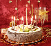 Celebratory table (cake and candles, two glasses with champagne,. Gift boxes) on red Stock Images
