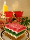 Celebratory table (Color Jelly cake on plate, two red glasses, f. Lowers and candle Stock Photos