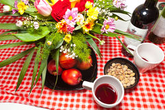 Celebratory table red wine flowers apples pistachios Royalty Free Stock Image