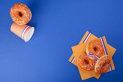 Celebrazione del giorno del ` s di re nei Paesi Bassi Feste di divertimento Accessori e dolci arancio su un fondo blu Spazio libe Fotografie Stock Libere da Diritti