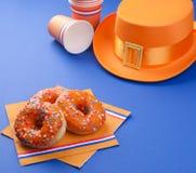 Celebrazione del giorno del ` s di re nei Paesi Bassi Feste di divertimento Accessori e dolci arancio su un fondo blu testo copia Fotografie Stock