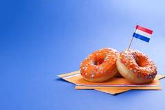 Celebrazione del giorno del ` s di re nei Paesi Bassi Feste di divertimento Donats dolci arancio su un fondo blu e sulle bandiere Fotografie Stock Libere da Diritti