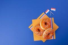 Celebrazione del giorno del ` s di re nei Paesi Bassi Feste di divertimento Donats dolci arancio su un fondo blu e sulle bandiere Fotografia Stock Libera da Diritti
