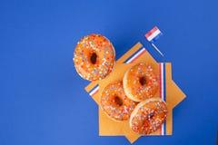Celebrazione del giorno del ` s di re nei Paesi Bassi Feste di divertimento Donats dolci arancio su un fondo blu e sulle bandiere Fotografia Stock