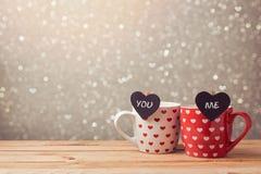 Celebrazione di festa di San Valentino con le coppie delle tazze e dei cuori sopra bokeh Fotografie Stock Libere da Diritti