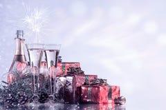 Celebrazione di natale e di nuovo anno Champagne, due vetri di vino, fuochi d'artificio e regali sul fondo di festa di lampeggiam Fotografia Stock