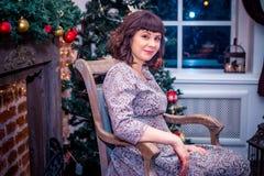 Celebrazione di natale La bella giovane donna nel vestito da sera sta una stanza decorata Fotografie Stock
