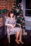 Celebrazione di natale La bella giovane donna nel vestito da sera sta una stanza decorata Fotografie Stock Libere da Diritti