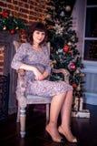 Celebrazione di natale La bella giovane donna nel vestito da sera sta una stanza decorata Fotografia Stock Libera da Diritti