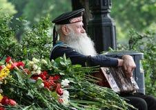 Celebrazione di Victory Day a Mosca Veterano della fine di seconda guerra mondiale su Marinaio con una fisarmonica che si siede s fotografia stock libera da diritti