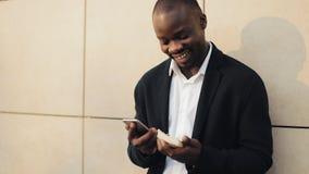 Celebrazione incoraggiante dell'uomo d'affari afroamericano felice esaminando telefono cellulare e tenendo una grande somma di de archivi video