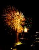 Celebrazione urbana del fuoco d'artificio sulle parti superiori illuminate del tetto Immagini Stock