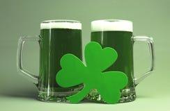 Celebrazioni del giorno di St Patrick felice con due grandi steins di vetro di birra verde Fotografie Stock Libere da Diritti
